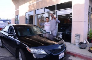 James Terry Jr. (right) flashes the Victory sign with Victory Autos Inc. owner and proprietor Heddy Trinidad after getting a new car because his old one had failed a smog test.