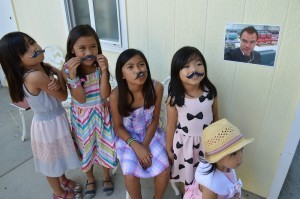 "Though physically absent, Lester ""attended"" the affair with his phot plastered on the wall, for a game- ""Pin the mustache on Lester's face,"" which the little girls eagerly played. (L-R: Jannelle's nieces Sophie, Mikey, Trisha, Simone, Hailey.)"