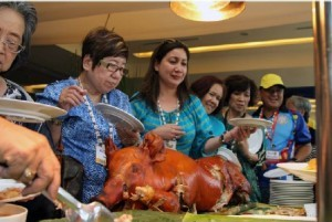 Fil-Ams partake of lechon (roasted pig) served during lunch for the 9th ACGTDT participants. Lunch was hosted by the Municipal Governor of Nasugbu, Batangas and the Department of Tourism-Southern Tagalog Regional Office last month.