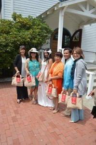 Guests pose with the bride, all wearing the wedding gift bag.