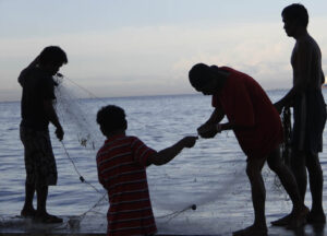 "Four fishermen prepare to cast their fishnet at a shallow portion of the Manila Bay along Roxas Blvd. on Tuesday morning (July 29, 2014). While Filipino fishermen seem to be ""content"" on using nets for a small catch, poachers using large fishing vessels have been raiding Philippine waters. (MNS photo)"