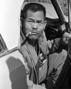 "California:. Larry Itliong, arriving at AWOC meeting in Central Valley,  sitting in a car with the door open, smoking a cigar. Early 1960's. ©1976 George Ballis/Take Stock / The Image Works        ""The Image Works""  ( photo courtesy of"
