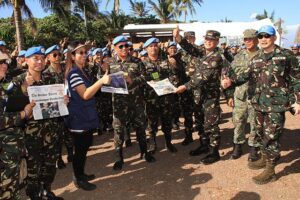 AFP chief General Gregorio Pio Catapang Jr. (3rd right) and DOH acting Secretary Janette Garin (3rd left) flash the thumbs up sign while giving copies of news articles about the peacekeepers, during their visit at the quarantine area in Caballo Island on Sunday, November 16. During the visit Catapang announced that the peacekeepers will be allowed to spend Christmas and New Year with their families, drawing loud cheers among the peacekeepers. (MNS photo)