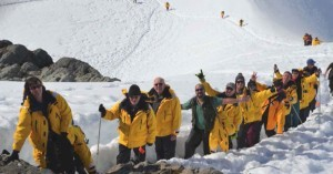 The Antarctica Expedition group of travelers and adventurers in front of the massive glaciers.