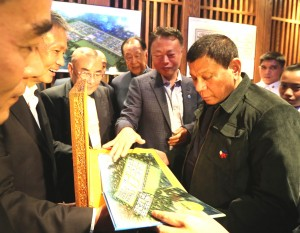 President Duterte looks at the perspective of the proposed Drug Addiction Treatment Center to be donated by the Friends of the Philippines Foundation: President Rodrigo R. Duterte looks at the architect's perspective and blueprint of the proposed Drug Addiction Treatment Center to be donated by the Friends of the Philippines Foundation during a lunch meeting at Dadong Roast Duck Restaurant in Beijing, China on Wednesday (Oct. 19, 2016). (Photo by King Rodriguez/PPD/PNA)